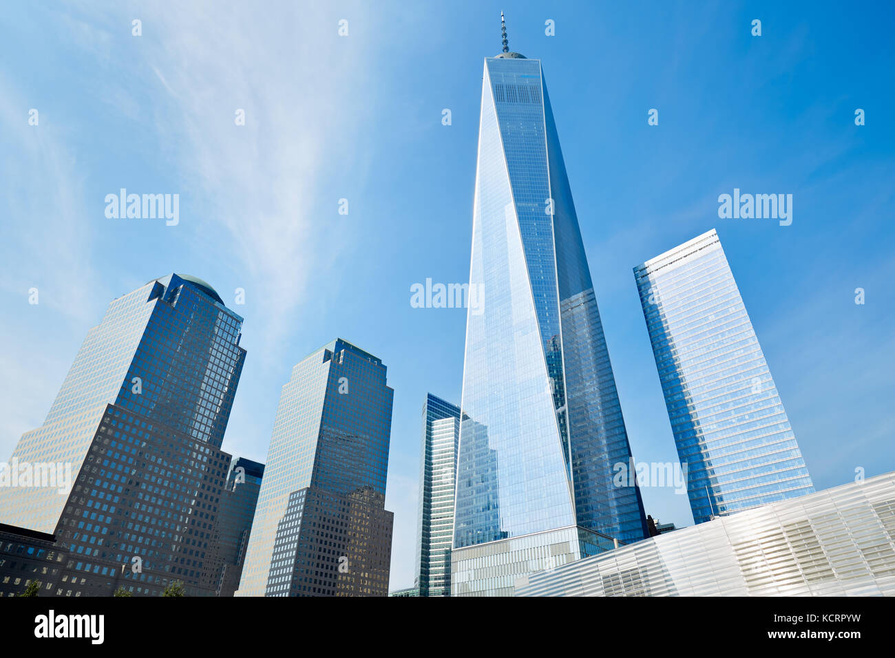 One World Trade Center skyscraper surrounded by glass buildings, blue sky in a sunny day in New York - Stock Image