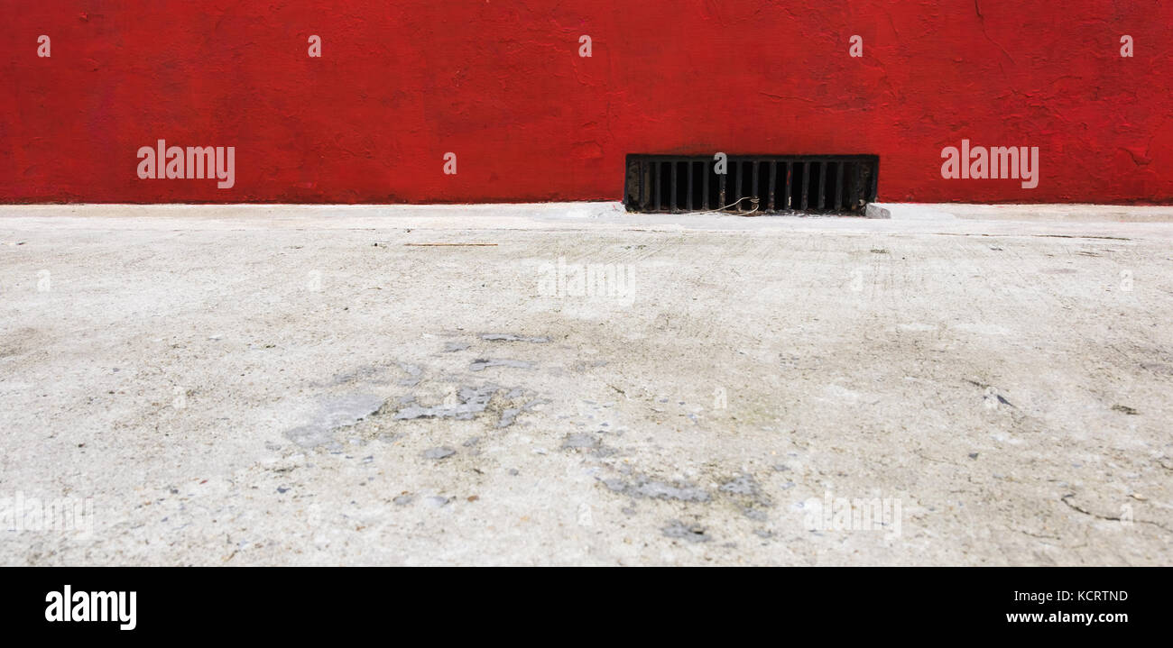 Red edging sidewalk with street drainage, selective focus. - Stock Image