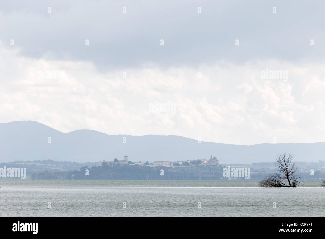 View of Castiglione del Lago town (Umbria, Italy), with Trasimeno lake and trees in the foreground Stock Photo