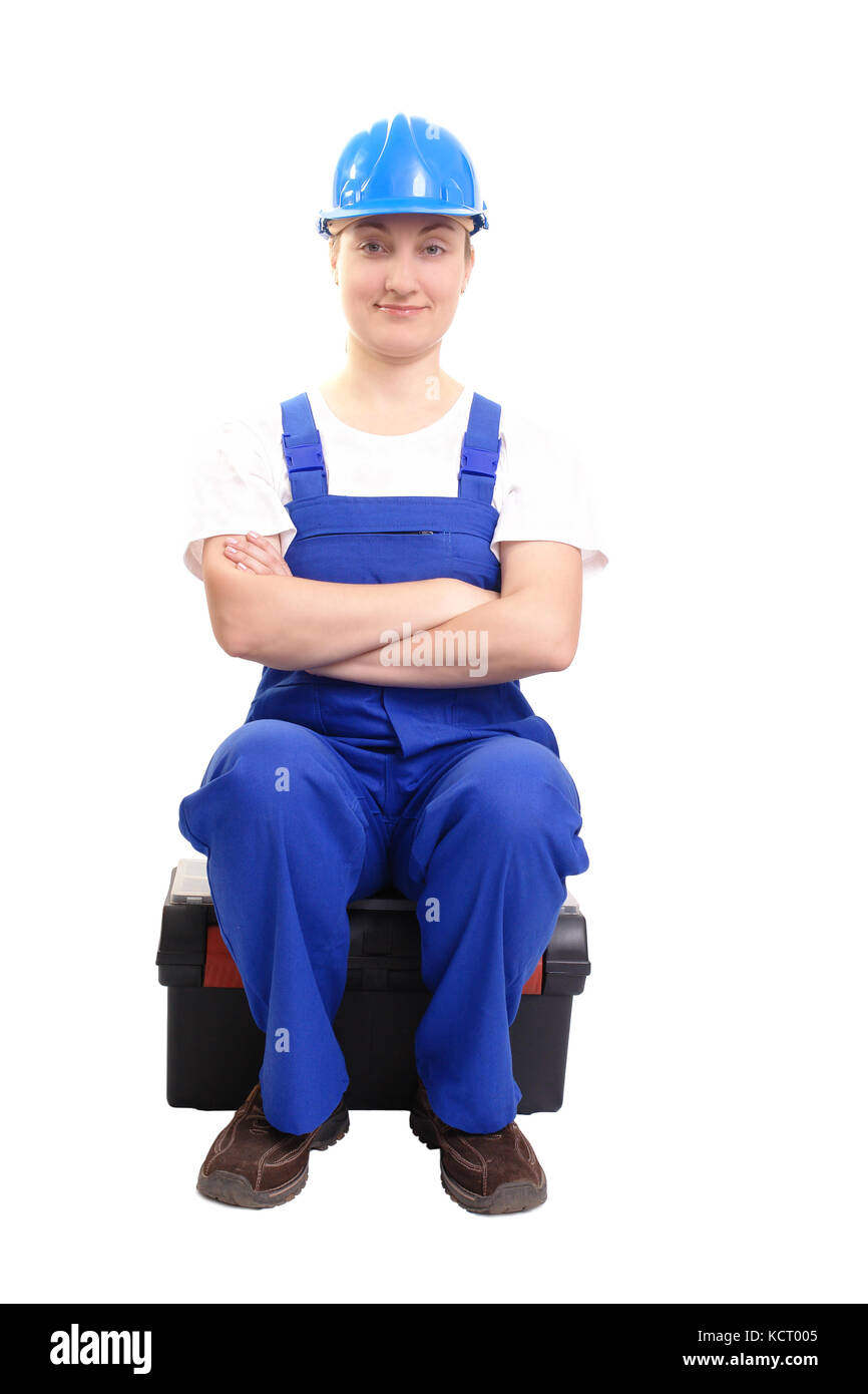 Service woman wearing blue helmet and overall sitting cross-armed on black toolbox over white - Stock Image
