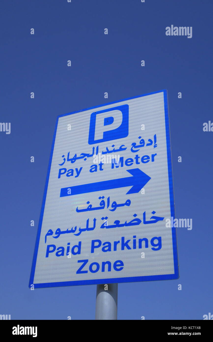 A road sign in Arabic and English informing drivers that they are in a paid parking zone and should pay at meter. - Stock Image
