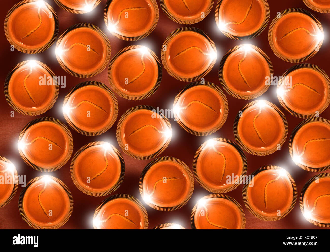 Stock photo of diwali greeting card showing top view of many illuminated diyas or oil lamps or panti forming shape Stock Photo