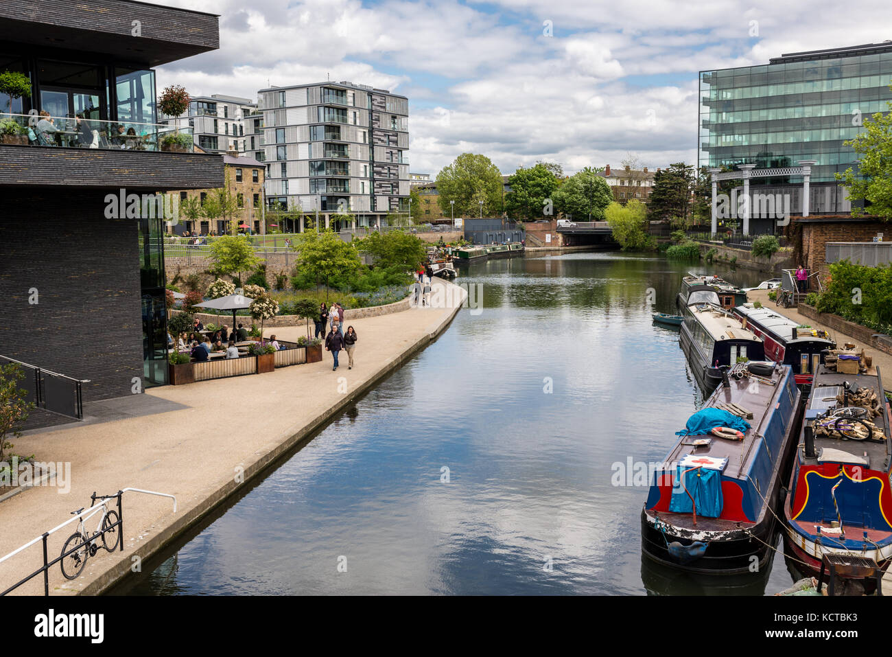 The canalside at Granary Square in the heart of King's Cross with people walking and barges on the canal. London, - Stock Image