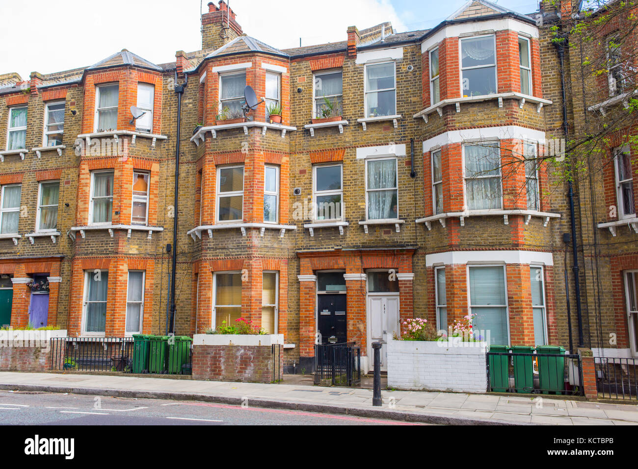 Classic British Victorian restored residential tenement building in red and yellow bricks with classic bay windows. - Stock Image