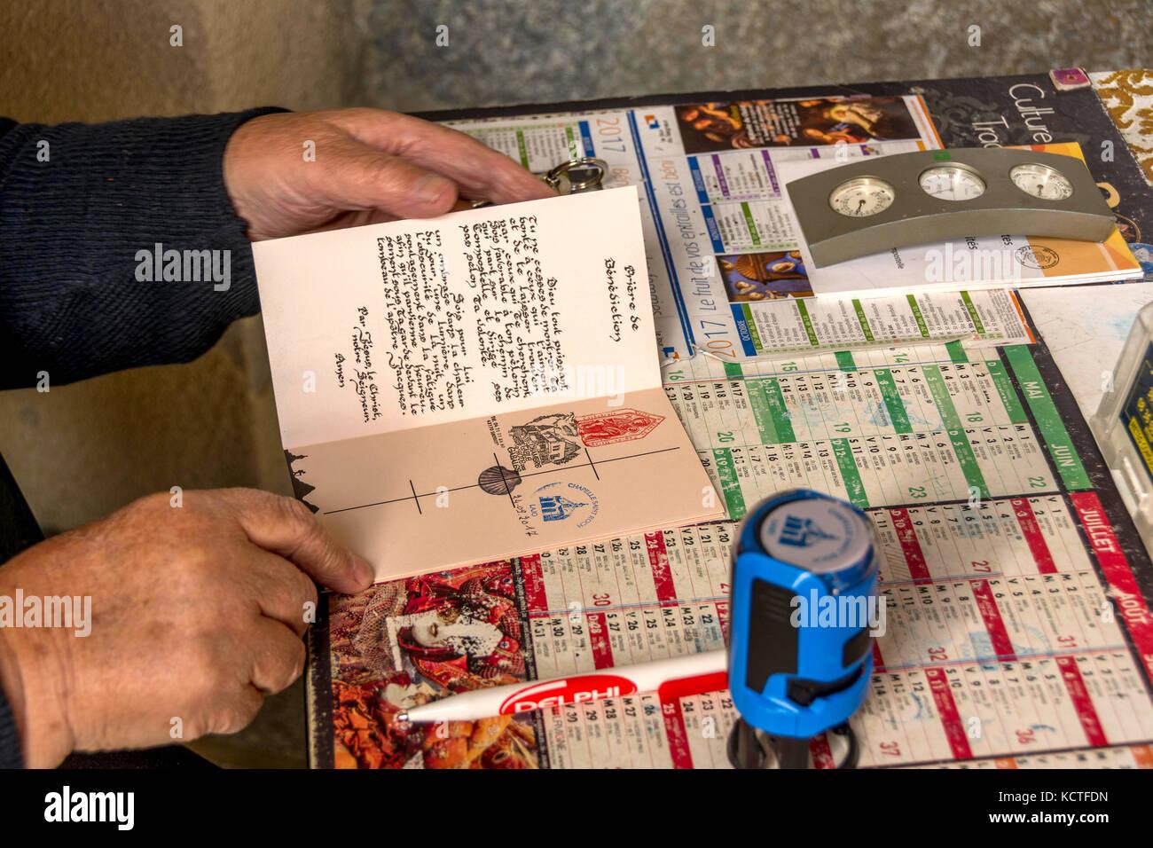 Person stamping a credential in the Saint Roch chapel on Via Podiensis. Camino de Santiago. Pilgrimage way. Haute - Stock Image