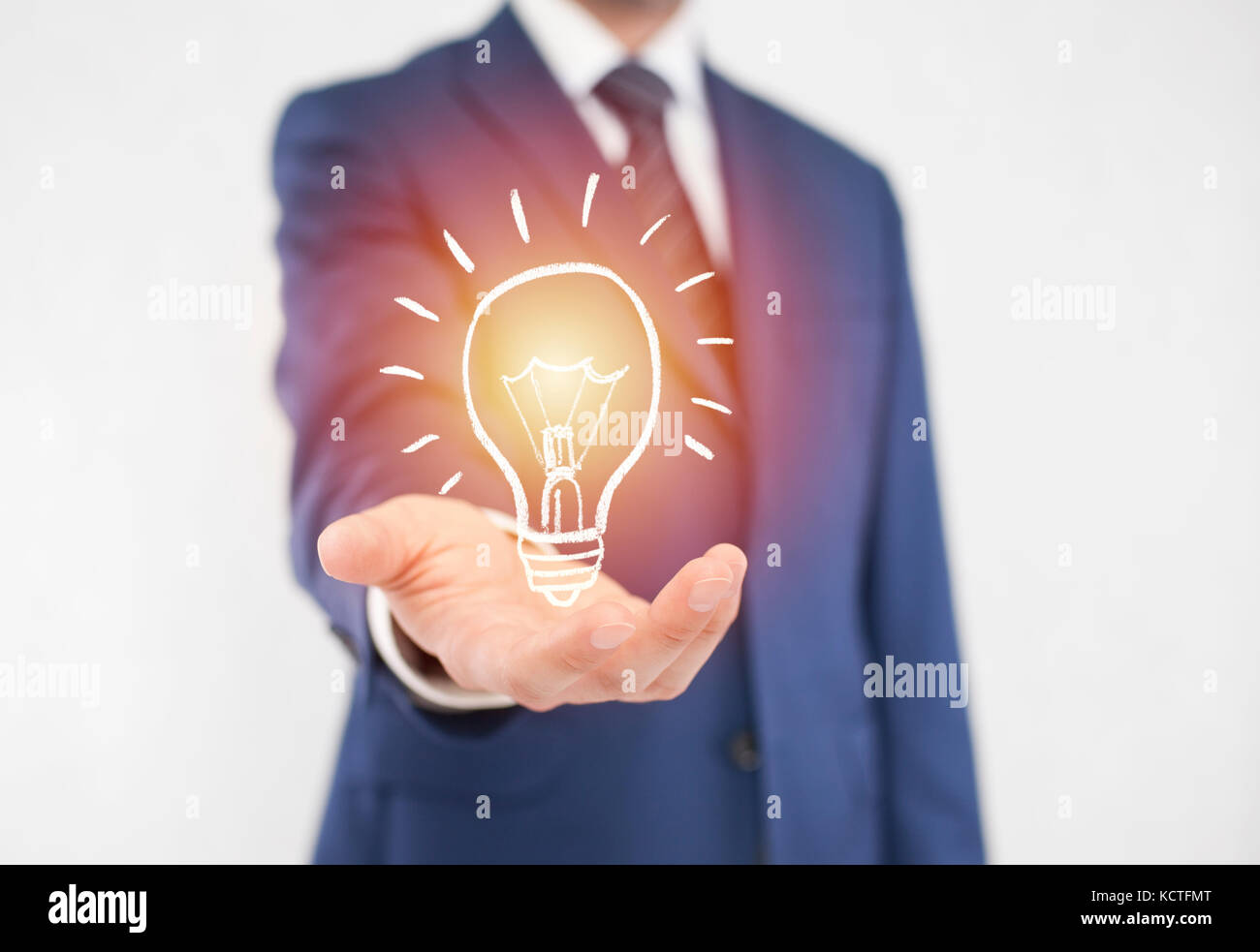 Businessman with idea light bulb - Stock Image