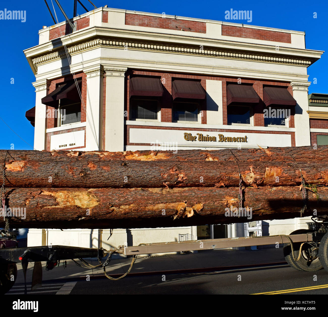 logging truck passes The Union Democrat Newspaper offices. Sonora, California - Stock Image