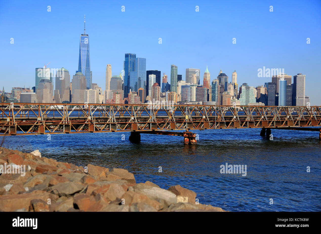 The skyline of Lower Manhattan financial district with foot bridge connect Ellis Island and Liberty State Park over - Stock Image