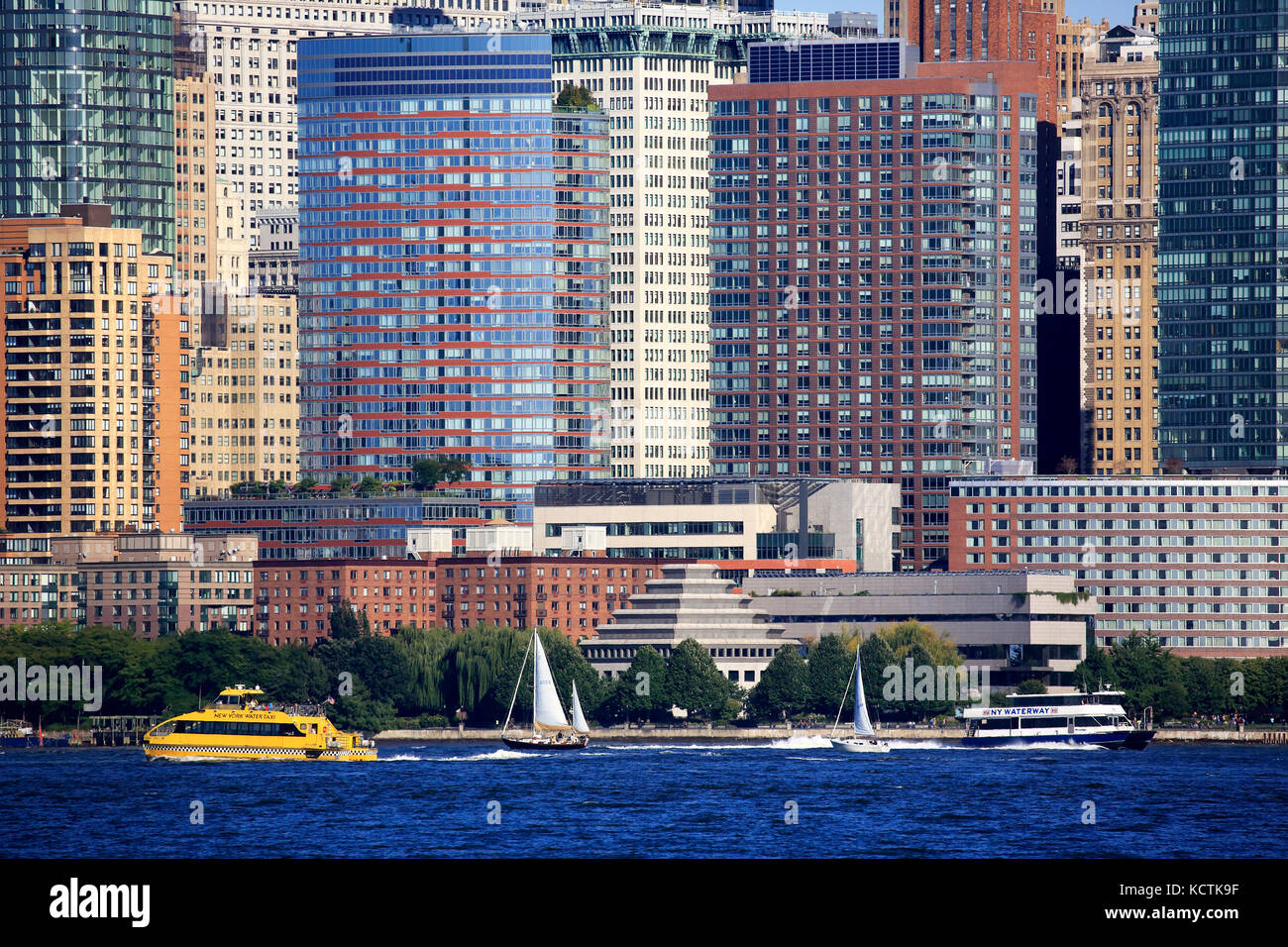 A closed up view of office towers in Lower Manhattan financial district with ferry boats in Hudson River in foreground.New - Stock Image