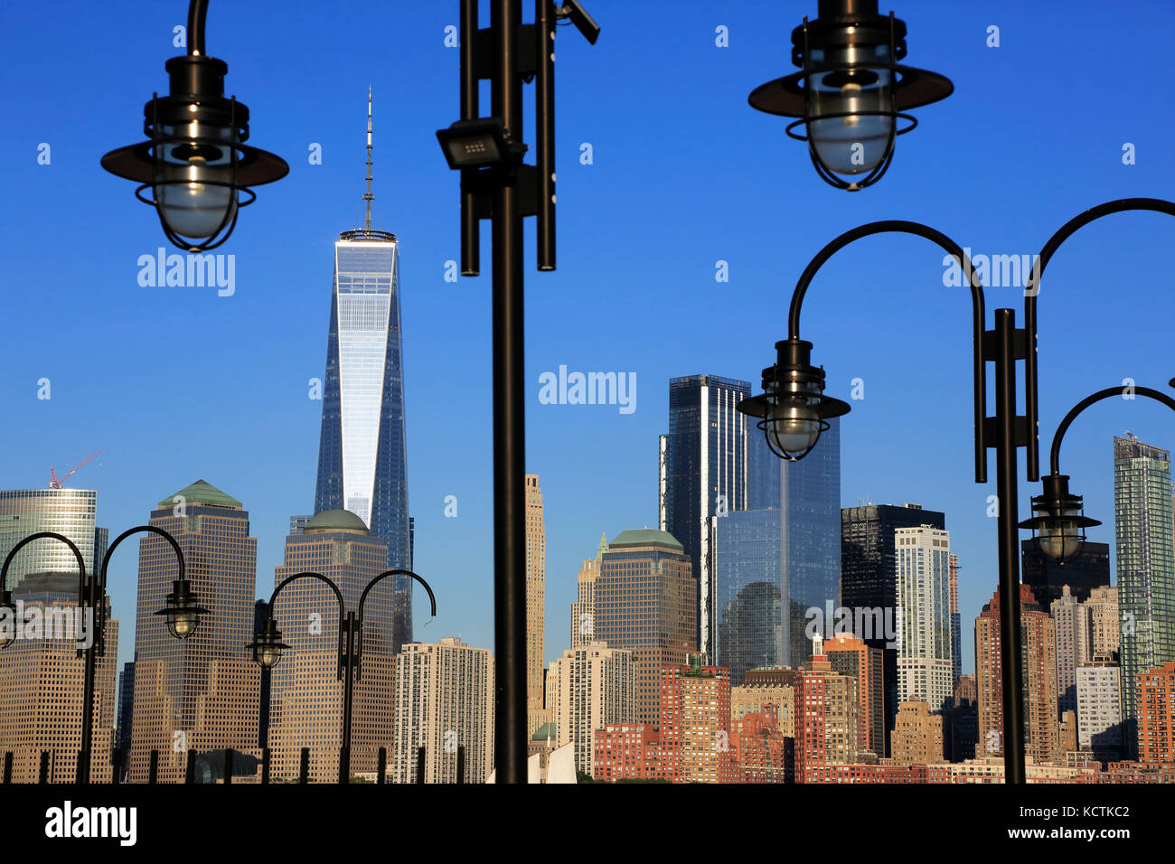 Skyline of Financial District in lower Manhattan with Hudson River and lampposts of old ferry dock of Liberty State - Stock Image