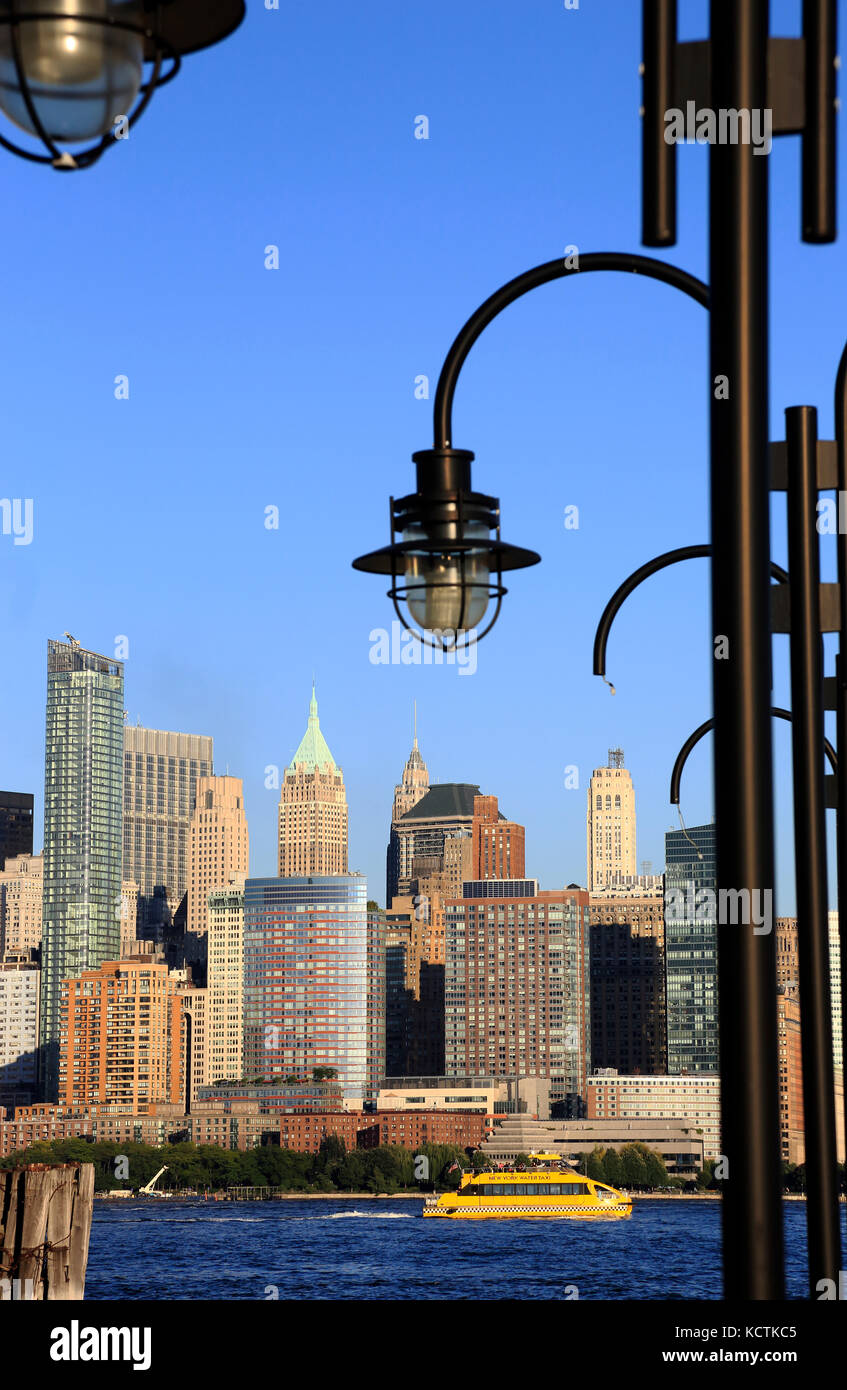 Skyline of Financial District in lower Manhattan with lampposts of old ferry dock of Liberty State Park in foreground.New - Stock Image