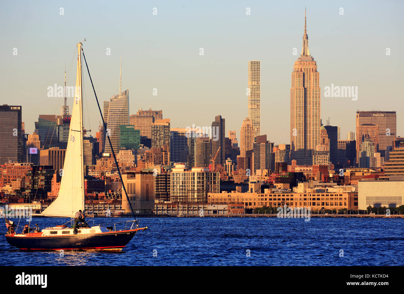 A sailboat in Hudson River with skyline of midtown Manhattan and Empire State Building in background.New York City.USA Stock Photo