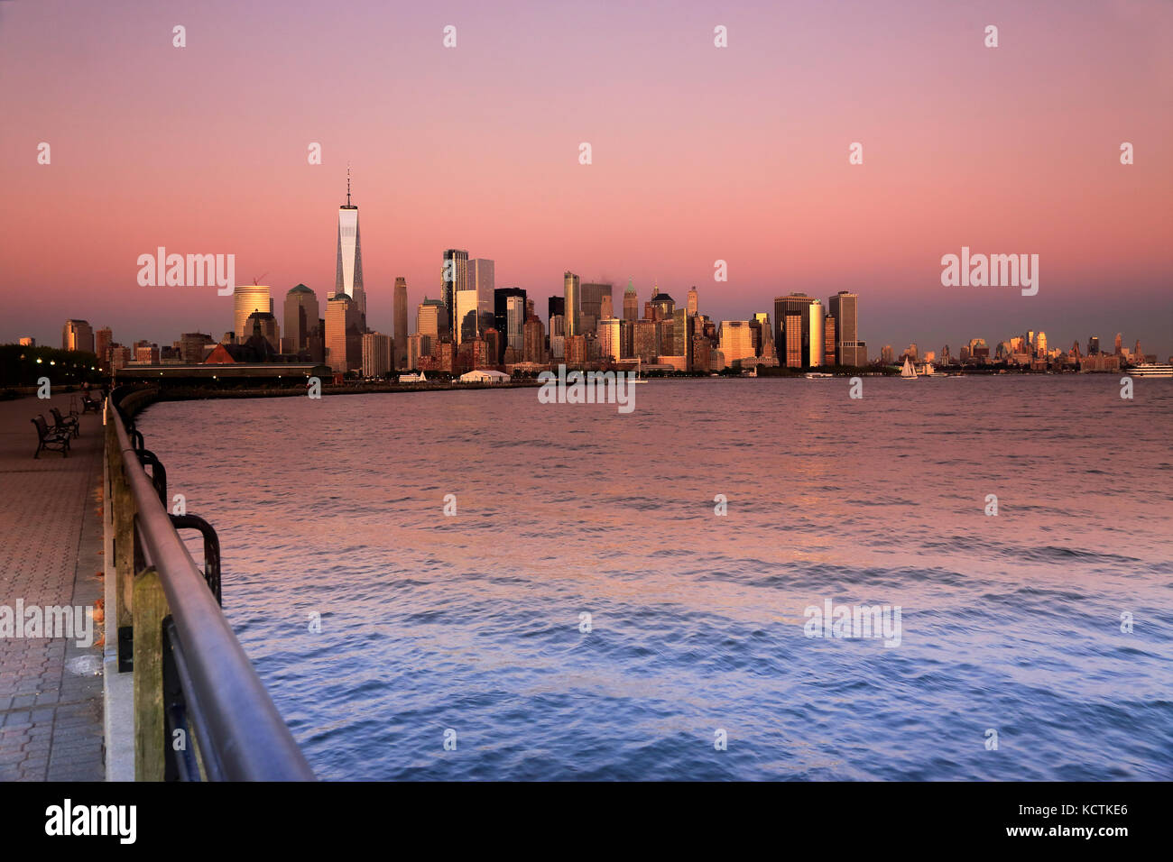 Sunset view of Lower Manhattan financial district with Hudson River in foreground.New York City,USA - Stock Image