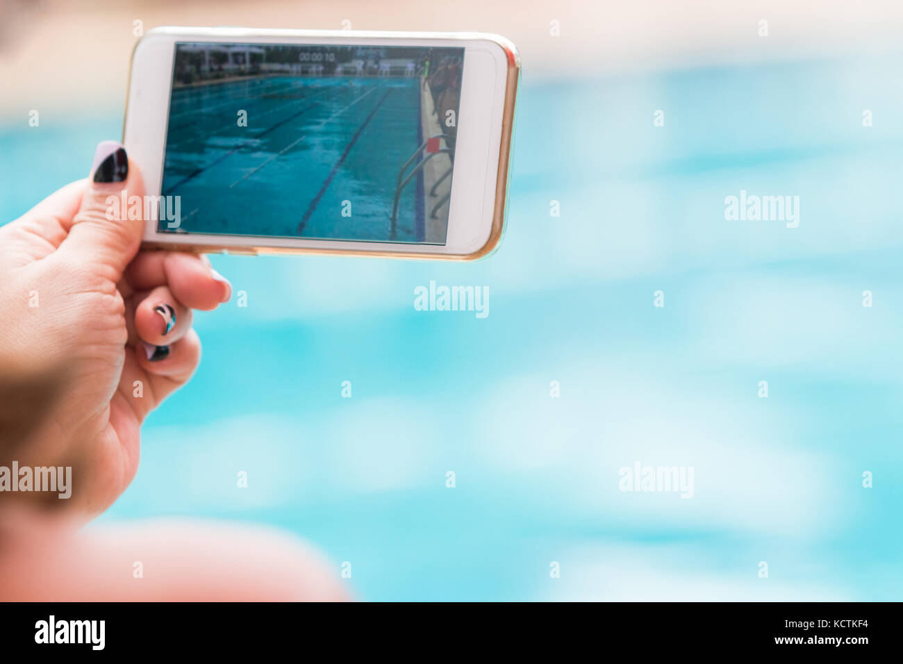 woman hand holding her phone recording swimming pool activities, selective focus, and room for text or copy space - Stock Image