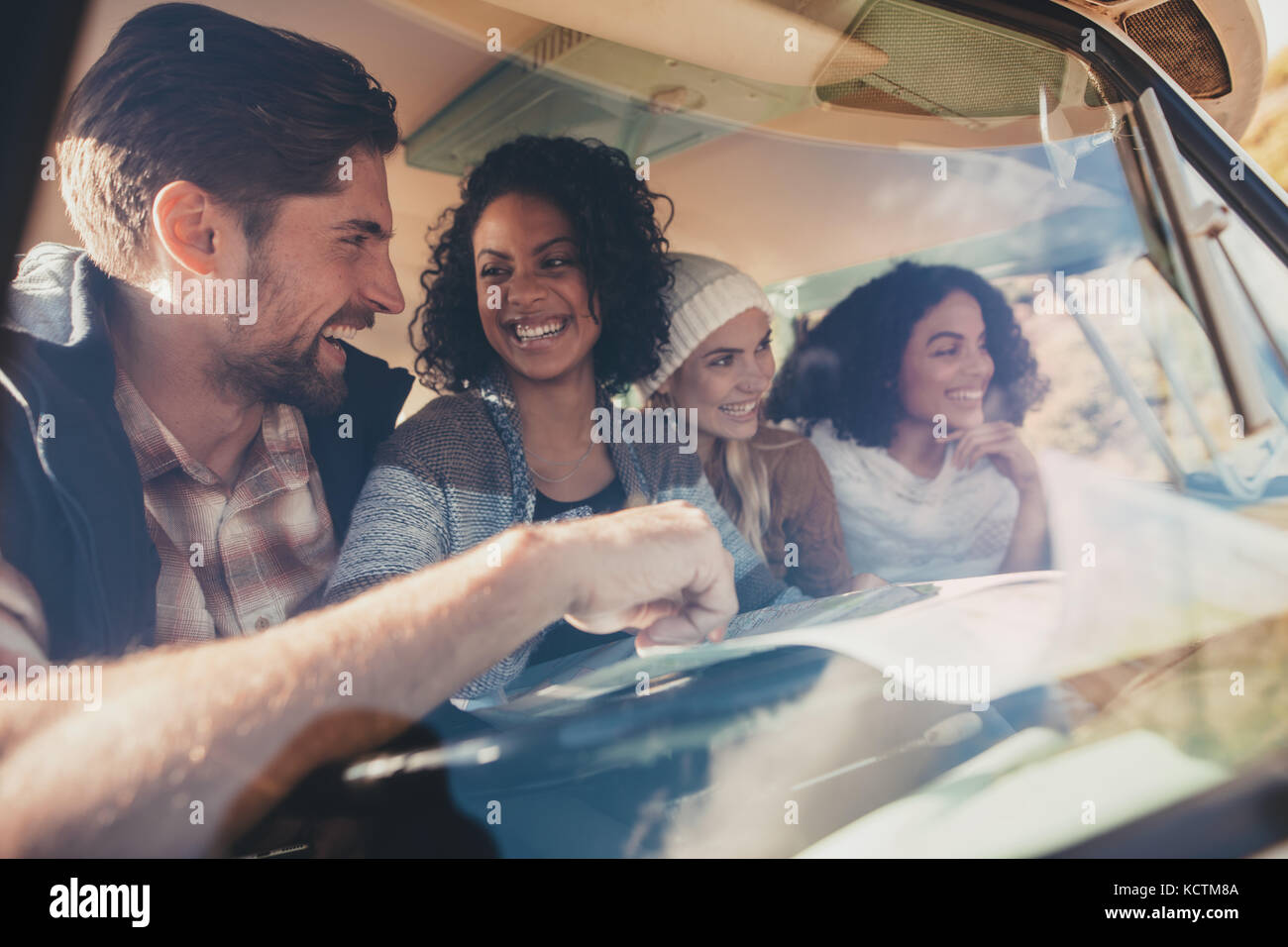Group of friends travelling in a van with map. Man discussing road trip route with female friends using a map. - Stock Image