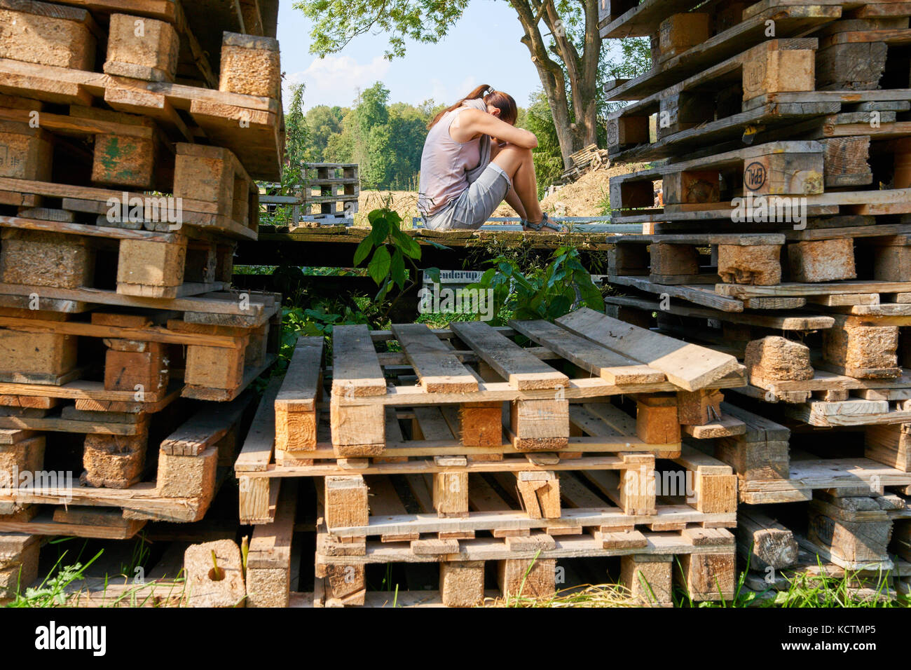 Woman in Munich, September 24, 2017 Woman in psychological crisis and depression sitting on wood pallets on September - Stock Image