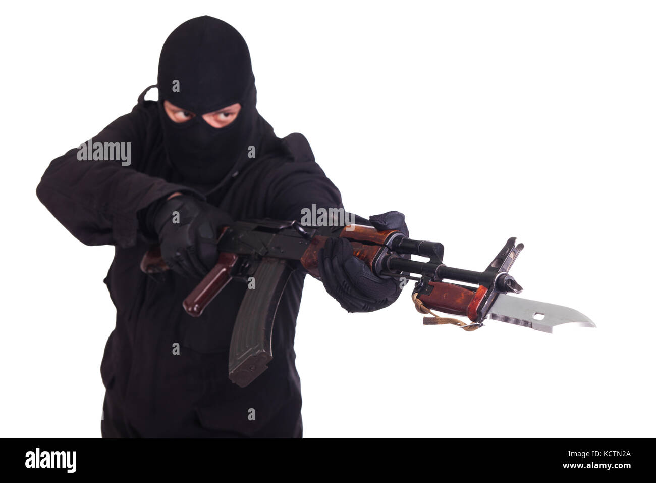man in black uniform and mask with AK 47 gun - Stock Image
