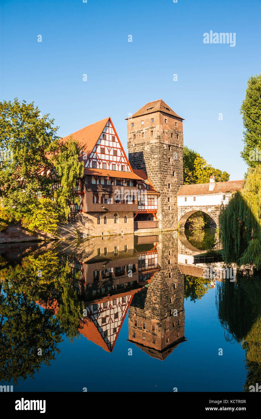 Hangman's Tower (Henkerturm) and traditional medieval half-timbered (fachwerk) house over the river Pegnitz in Nuremberg, - Stock Image
