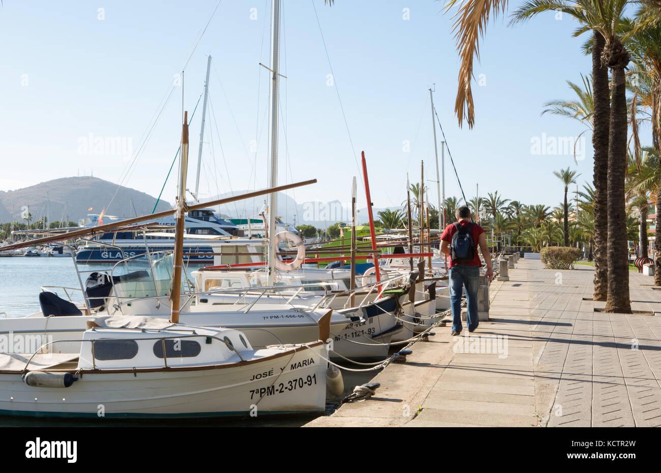 Man walking at harbour, sailing boats tied to mooring post, Puerto de Alcudia, Alcudia, Majorca, Balearic Islands, - Stock Image