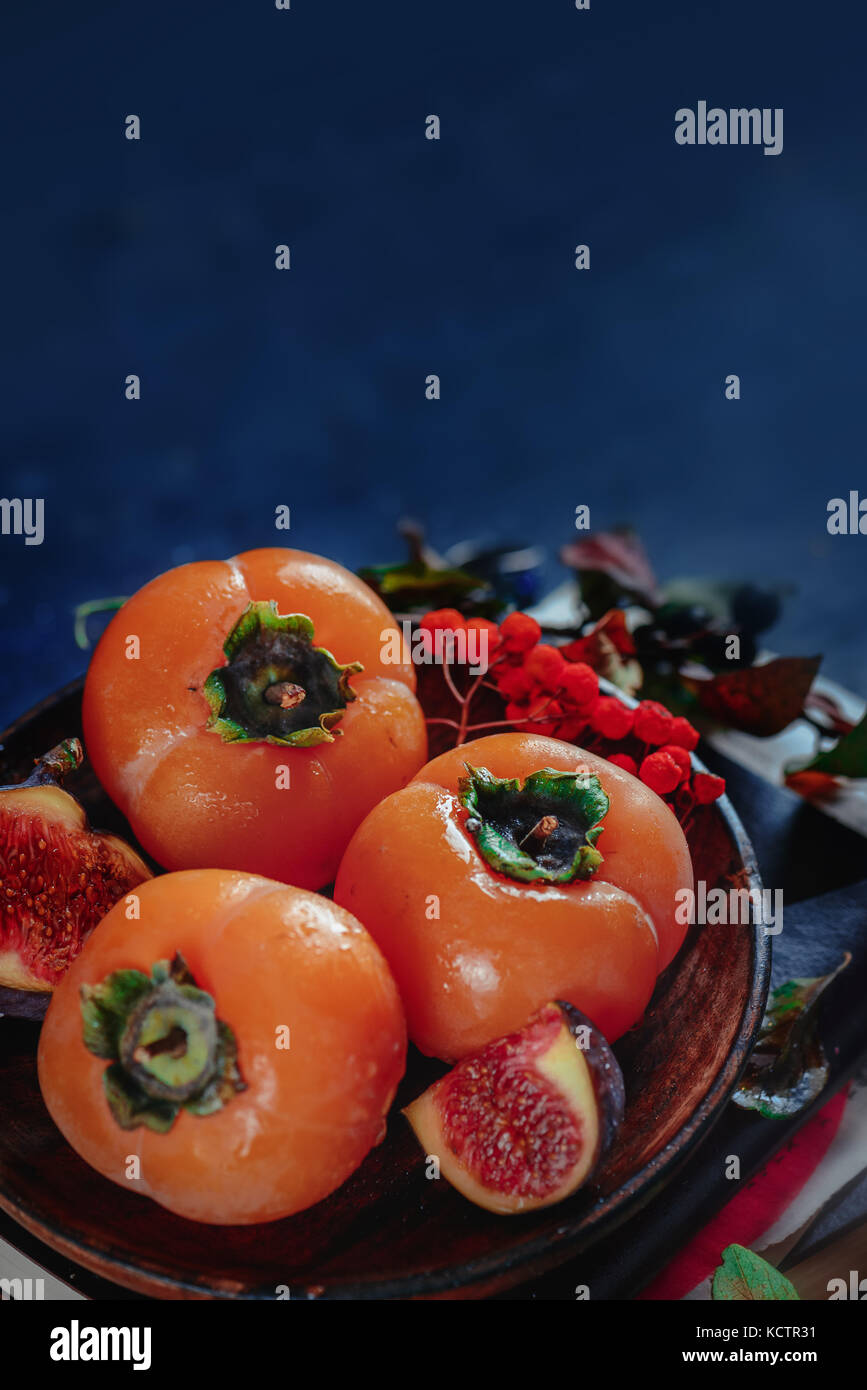 Dark autumn still life, ripe persimmons on a wooden plate with autumn leaves. Seasonal fruits close-up. Dark food - Stock Image