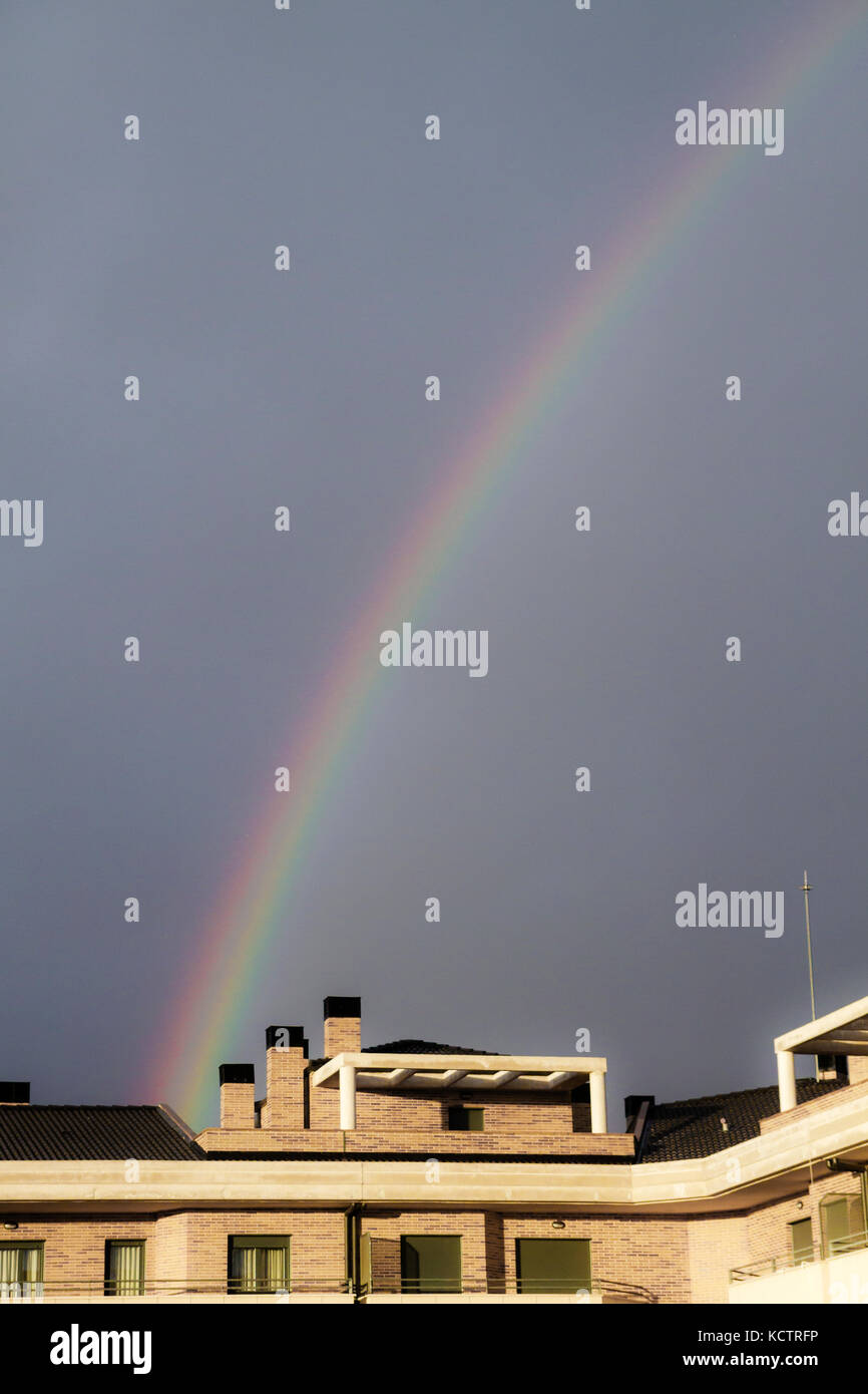 rainbow in a blue sky over the houses of the city after a storm - Stock Image