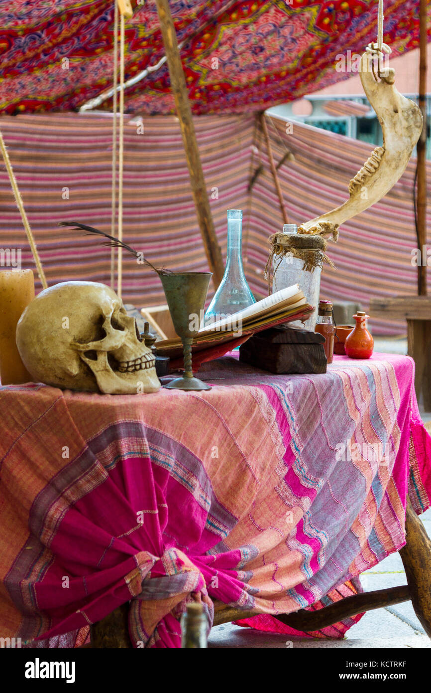table with potions, books and skull of medieval times, witchcraft and medicine. - Stock Image