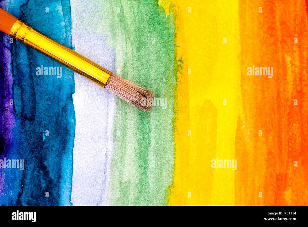 Paintbrush on rainbow watercolour hand drawing backgrounds. Close-up. - Stock Image