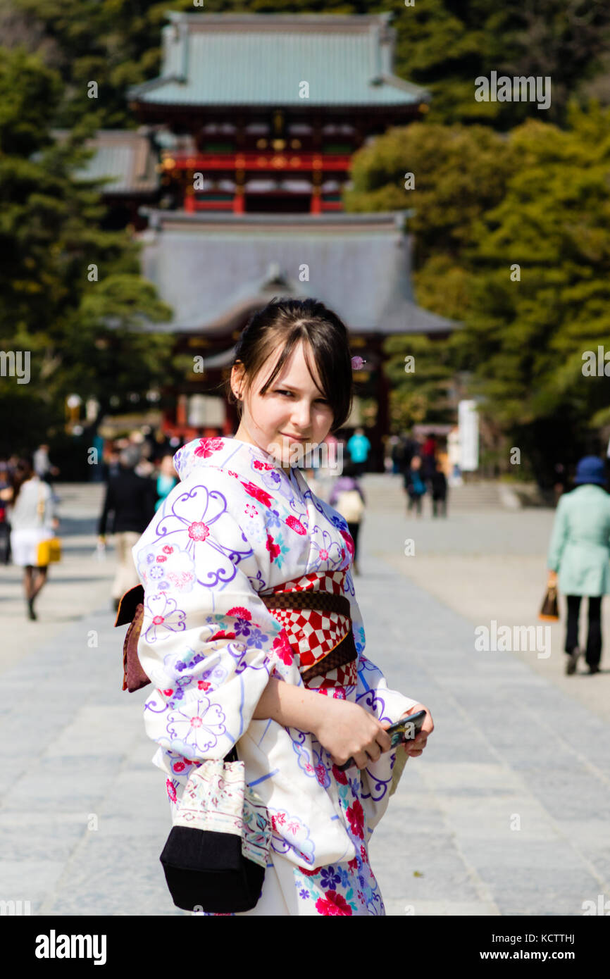A beautiful young girl wearing a kimono while on holiday in Japan, stood in front of a temple in Kamakura, Japan. - Stock Image