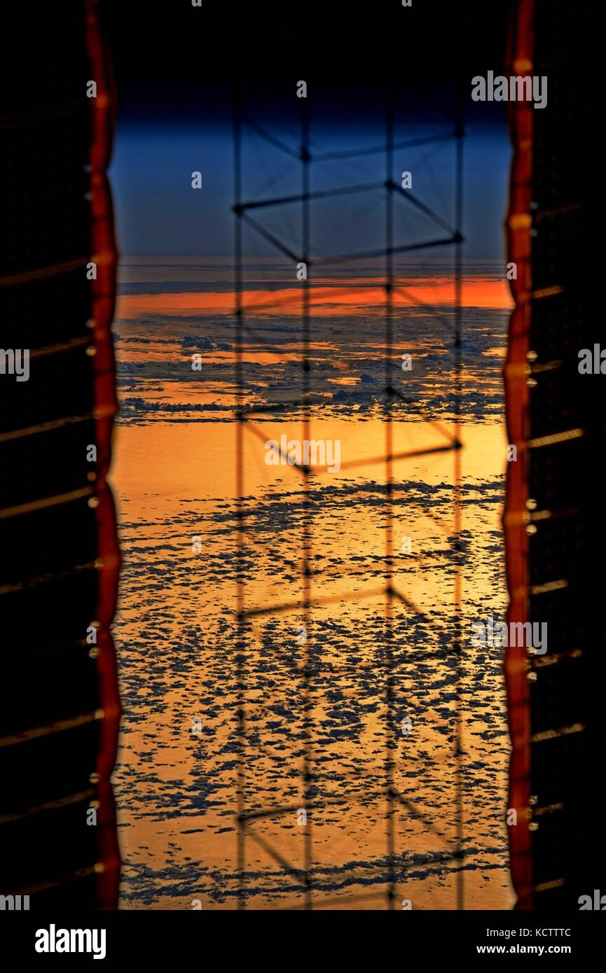 View from Earth Orbit of a sunset over the planet surface reflected off a solar array from the International Space - Stock Image