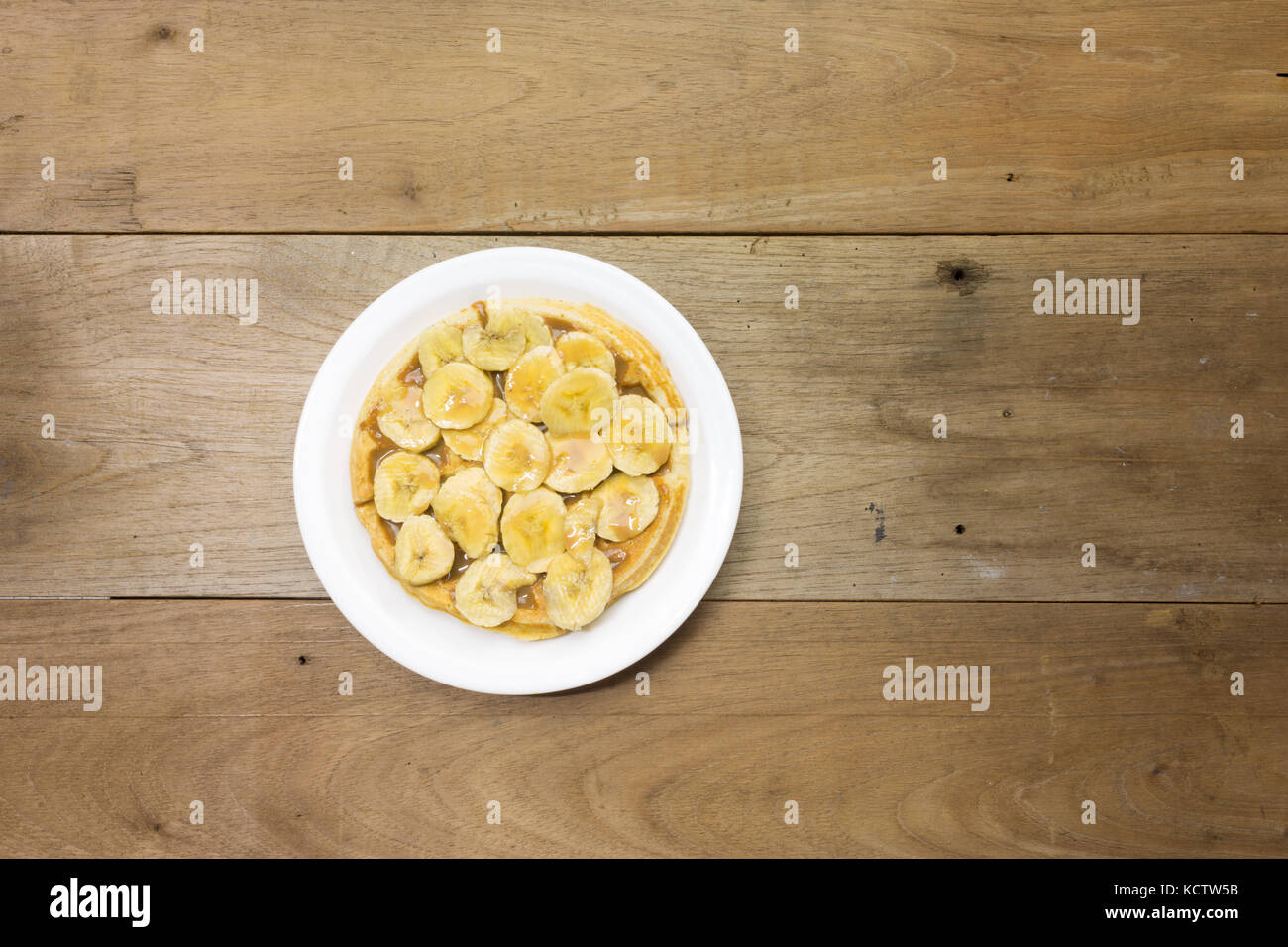 Waffle with milk caramel spread (Spanish: Dulce de leche) and banana slices on white plate, on wooden background, - Stock Image