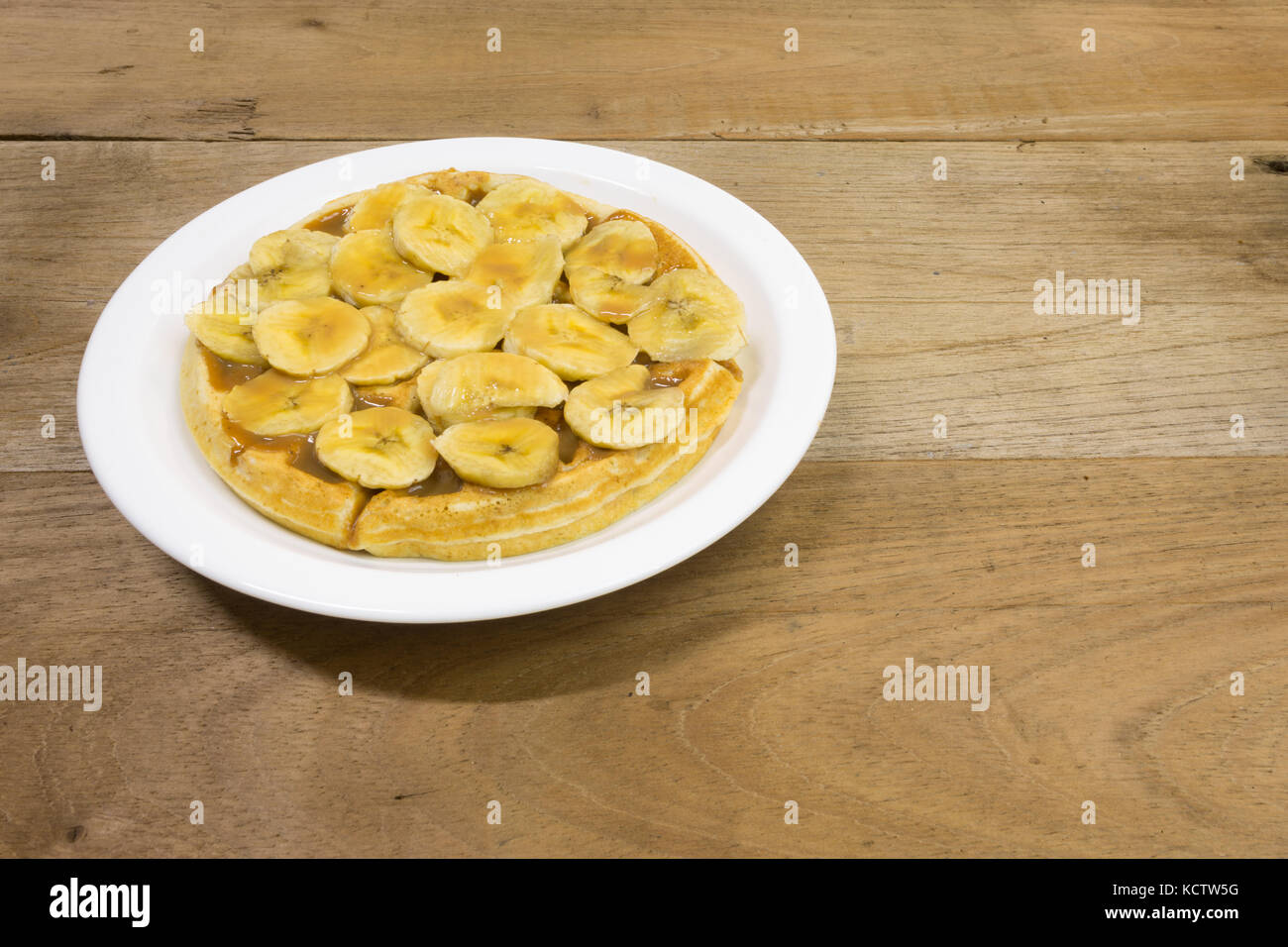 Waffle with milk caramel spread (Spanish: Dulce de leche) and banana slices on white plate, on wooden background - Stock Image