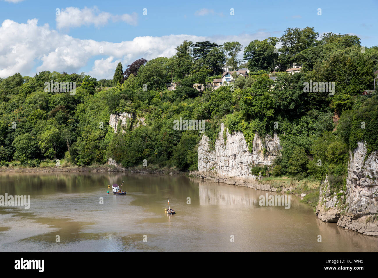 Cliffs with overlooking houses on the River Wye at Chepstow, Wales, UK - Stock Image