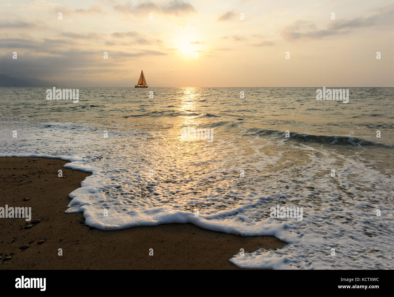 Sunset sailboat is a sailboat sailing along the ocean at sunset with the moon rising in the sky as a wave rolls Stock Photo
