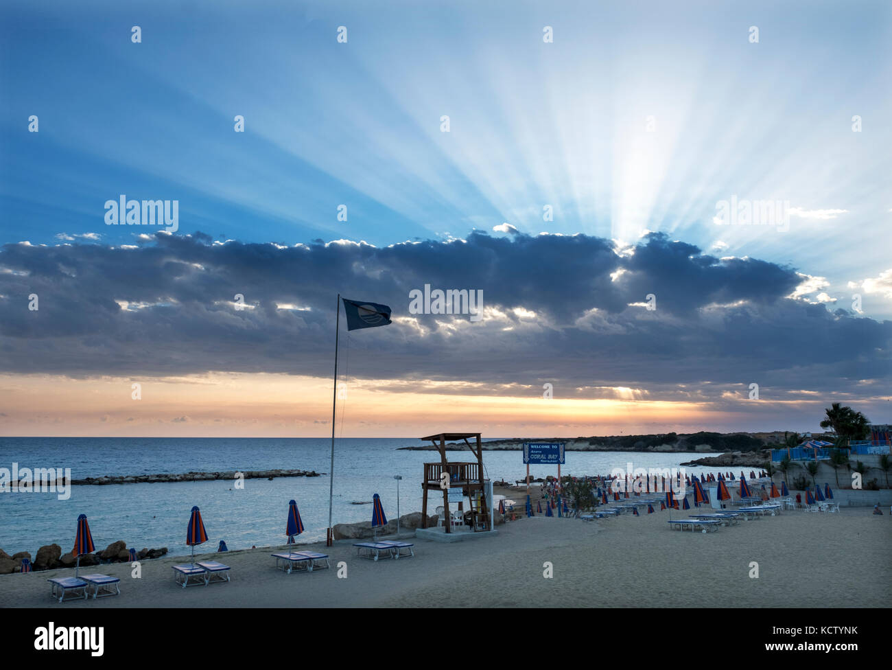 Sunrays burst through from behind the clouds at Coral Bay in the Peyia district, near Paphos, Cyprus. - Stock Image