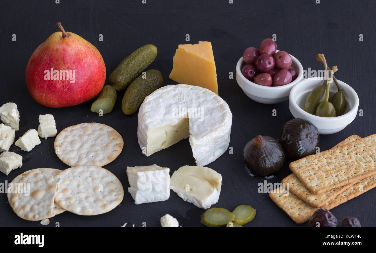 Cheese,crackers, pickles and fruit on black background close up - Stock Image