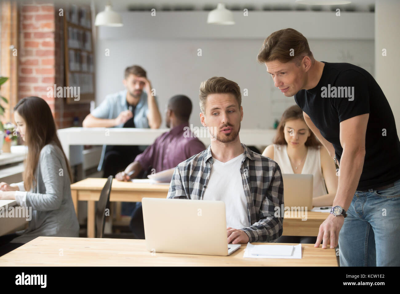 Casual entrepreneur explaining business project to his coworker. Two young employees discuss work-related goals - Stock Image