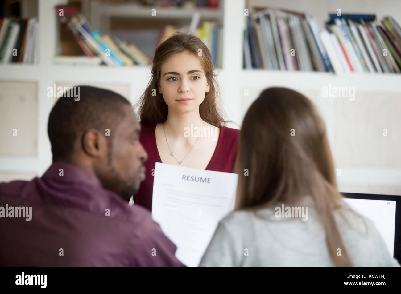 Multiethnic HR team discuss female job applicants resume. African american human resources representative listening - Stock Image