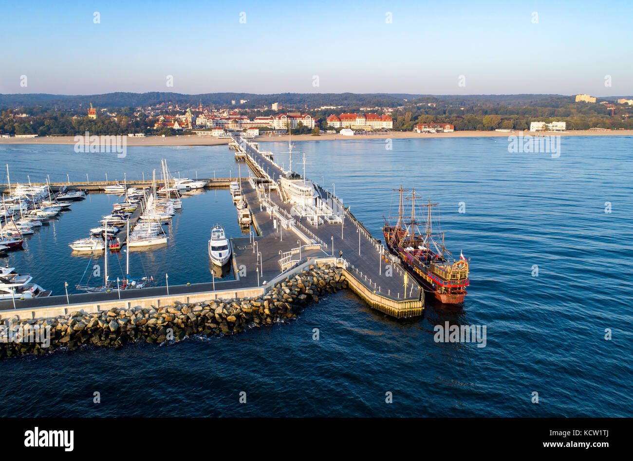 Sopot resort in Poland. Wooden pier (molo) with marina, yachts, pirate tourist ship, beach, vacation infrastructure. - Stock Image