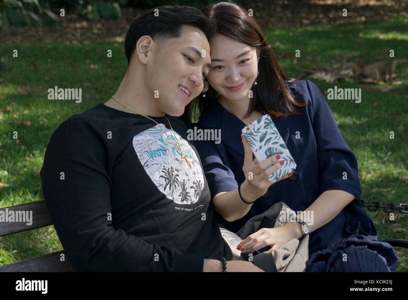 Two attractive Korean Americans take a selfie on a bench in Washington Square Park in Greenwich Village, New York - Stock Image