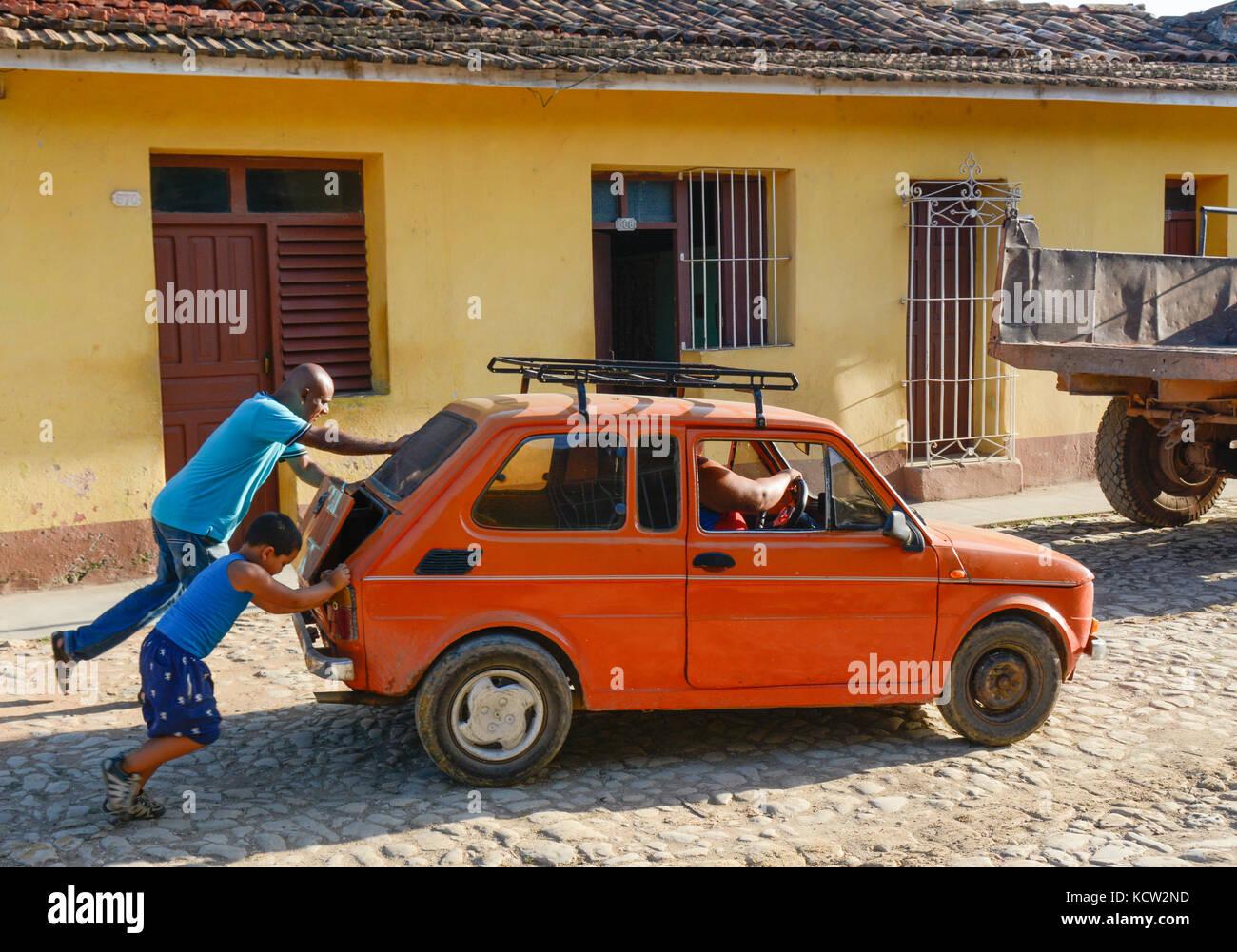 Push starting old car in Trinidad,  Cuba - Stock Image