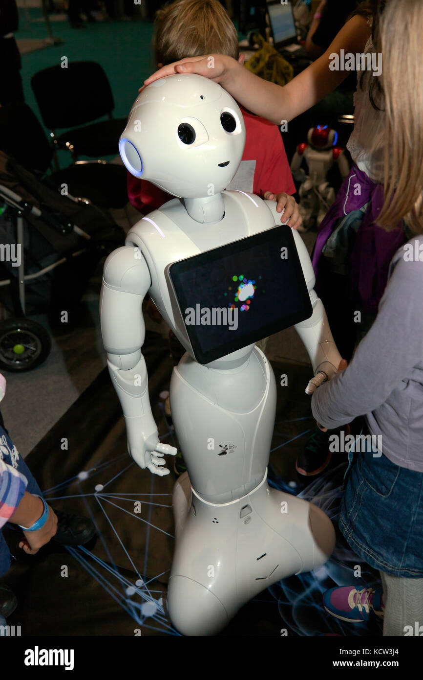 Children interacting with Pepper, a humanoid social robot,  in the Robot Zone at New Scientist Live 2017 - Stock Image