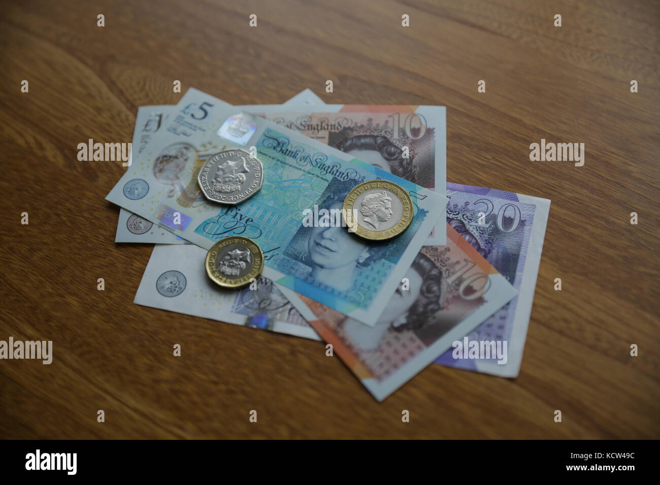A selection of British currency on a wooden surface Stock Photo