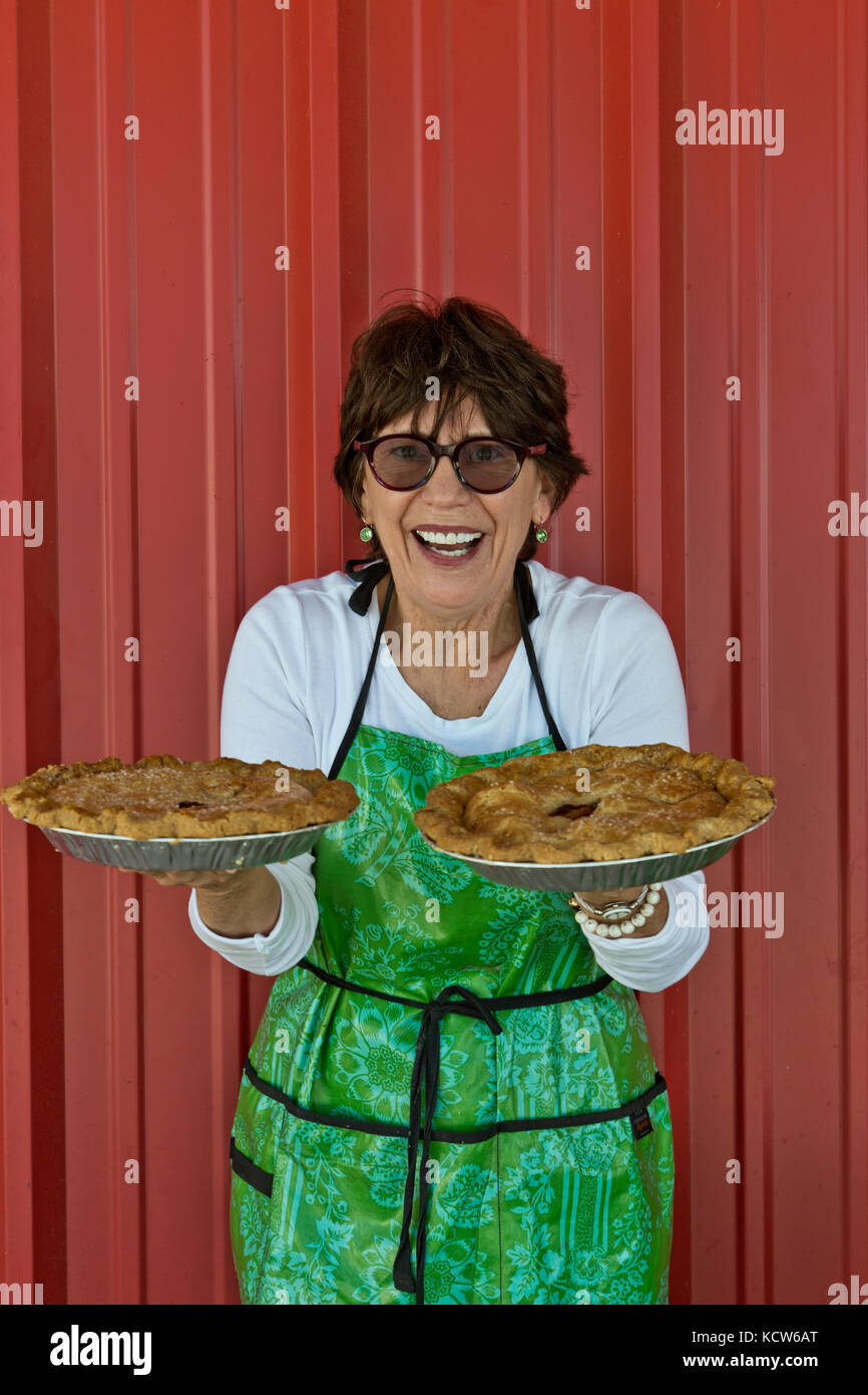 Proud & happy female baker displaying her 'specialty'  apple & peach pies. - Stock Image