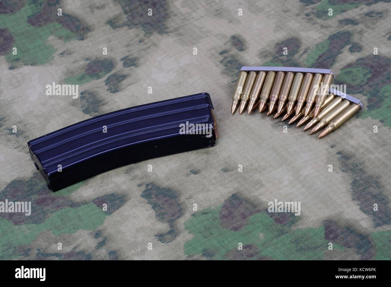Ammunition with magazine on camoflage background - Stock Image