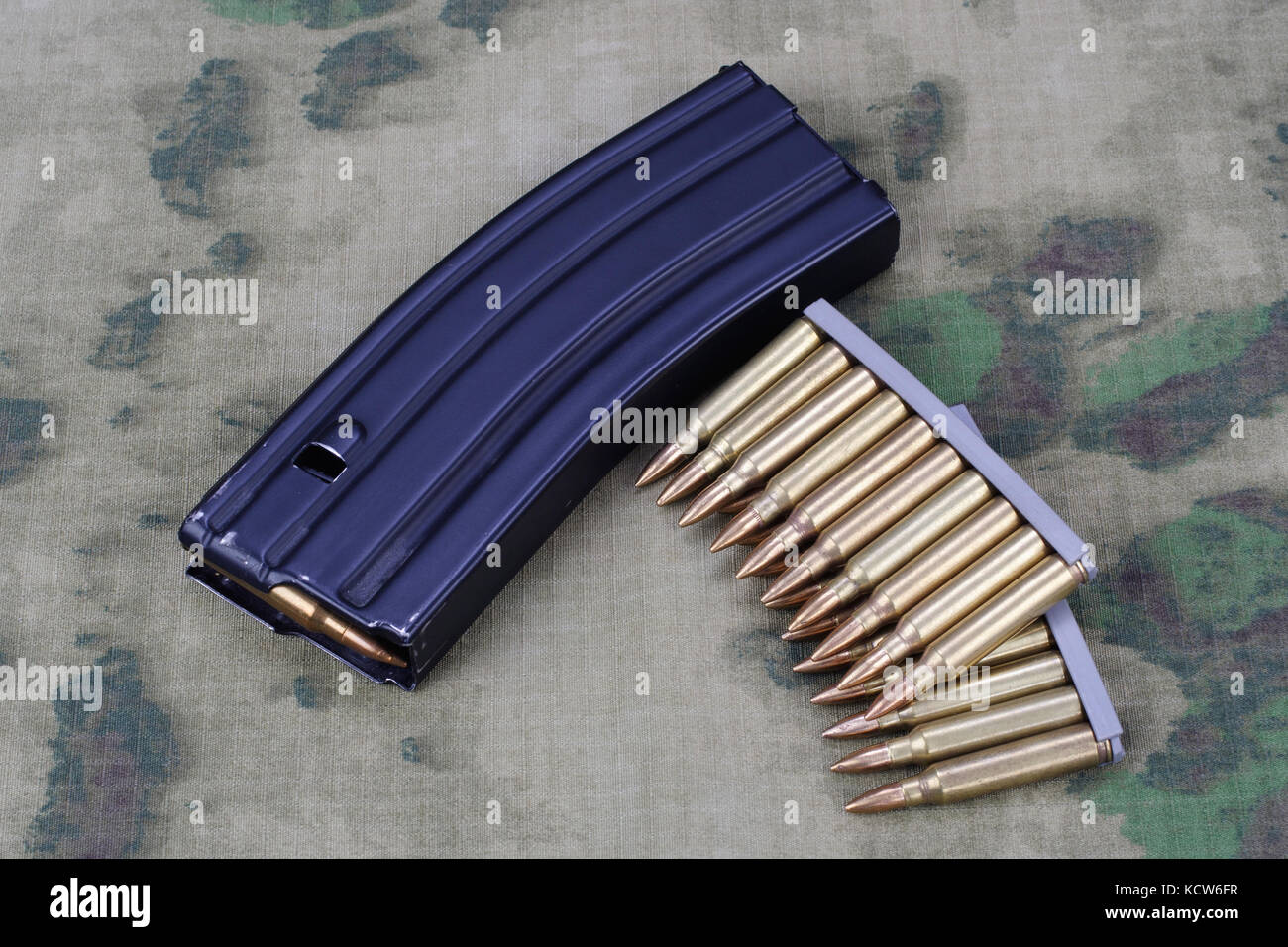 Ammunition with magazine on camoflage background - Stock Image