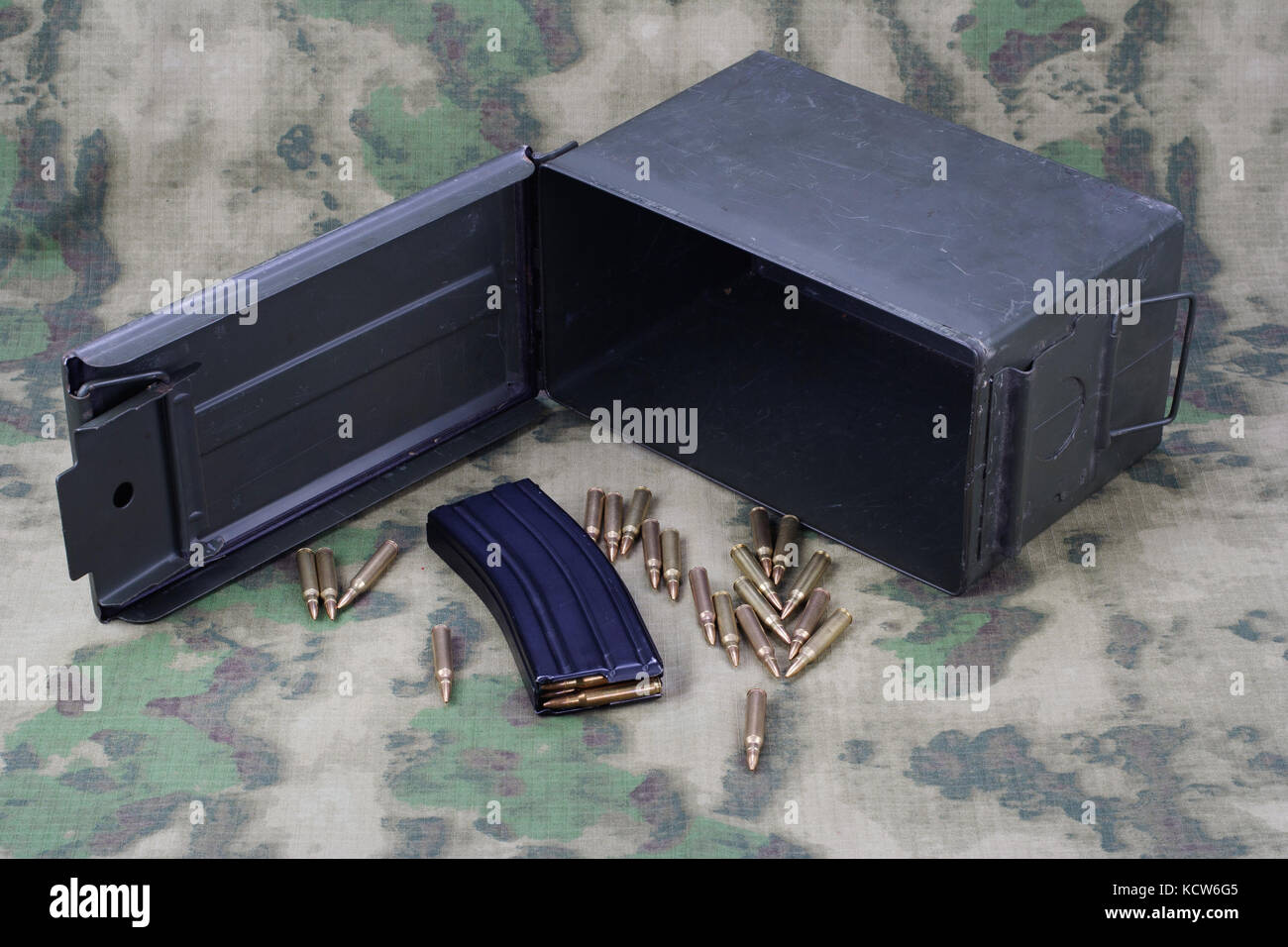 Ammo Can with ammo on camoflage background - Stock Image