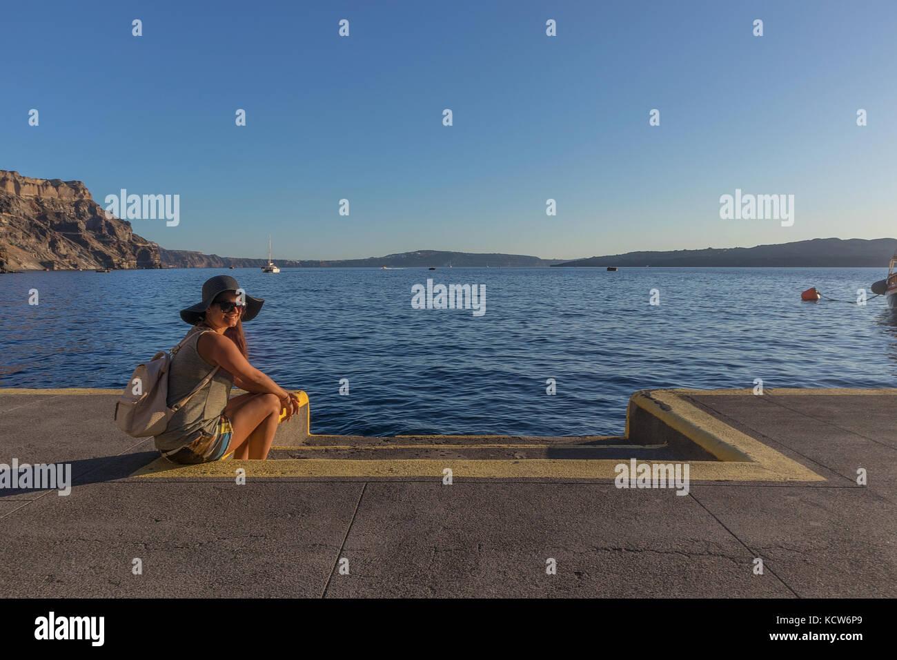 SANTORINI/GREECE 05 SEP 2017 - Young girl sitting in the port of Fira. Santorini, Greece. - Stock Image