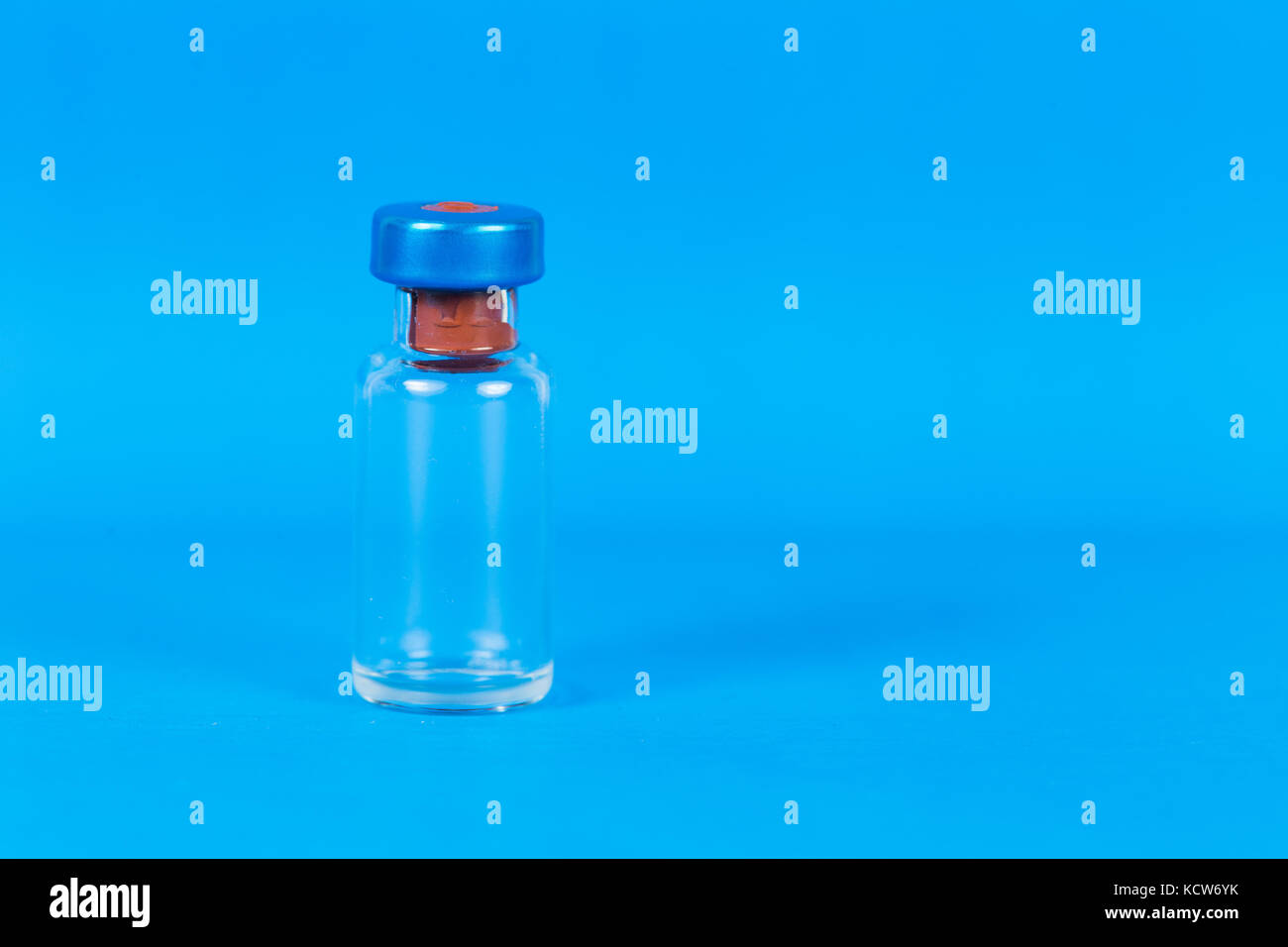 An empty vaccine vial taken in an isolated blue background - Stock Image