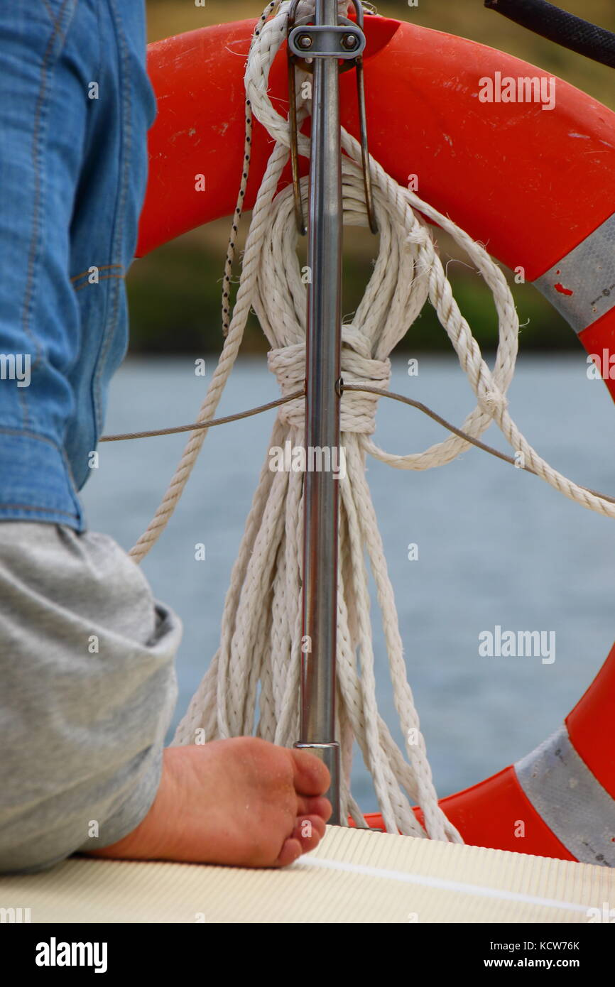 Limited view from behind of a young woman on the deck of a yacht on a blustery day with an orange life buoy in the - Stock Image