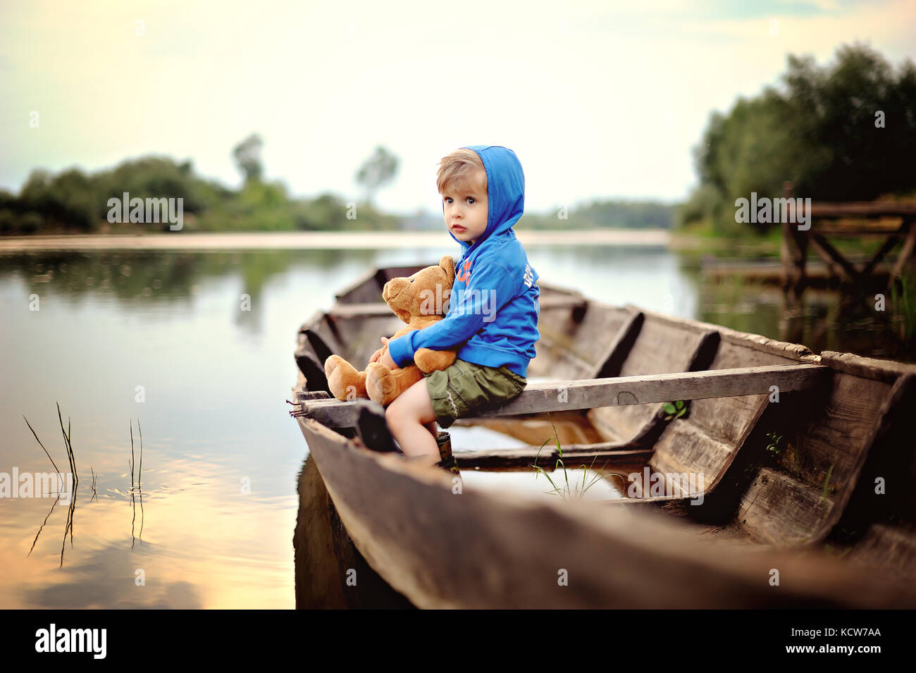 A small, pensive boy in a blue hooded sweater sits on wooded boot with  teddy bear - Stock Image